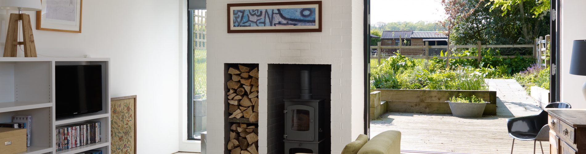 Picture of a Frame Technologies self build home living room with open door on to patio, wood burner and sofa